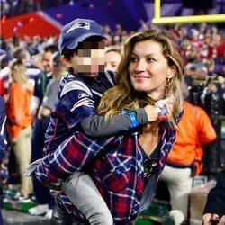 Gisele Bundchen con camisa de cuadros y vaqueros en un partido de la Super Bowl con su hijo