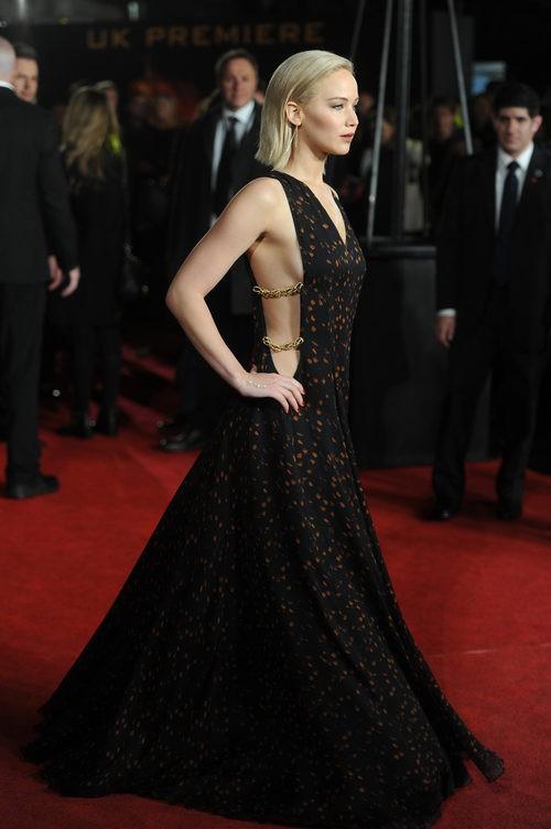 Jennifer Lawrence con vestido negro con motas naranjas y cadenas laterales de Dior en el photocall de la premiere de 'Los Juegos del Hambre'