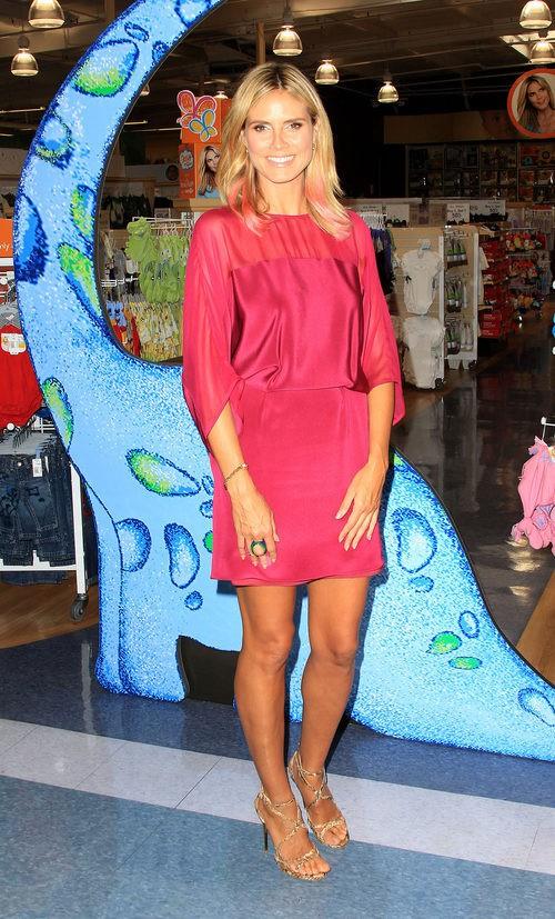 Heidi Klum con vestido corto fucsia en la presentación de su colección de ropa