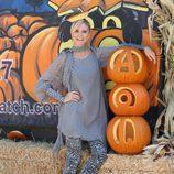 Heidi Klum con blusón y vaqueros junto a una calabaza gigante