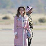Rania de Jordania con abrigo en tweed y vestido azul en su llegada al aeropuerto de Madrid