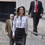 Rania de Jordania con falda de tubo midi en cuero negro y blusón con lazada al cuello  en  su visita al centro cultural Medio-lab prado