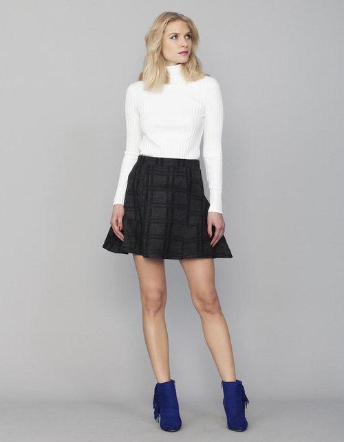 Jersey de cuello alto blanco y falda de cuadros grises y negros de la colección Tartán de Invierno 2015/2016 de Blanco