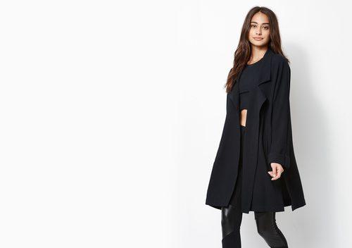 Modelo con conjunto negro de top, pantalón de cuero y abrigo de Kendall y Kylie Jenner para PacSun