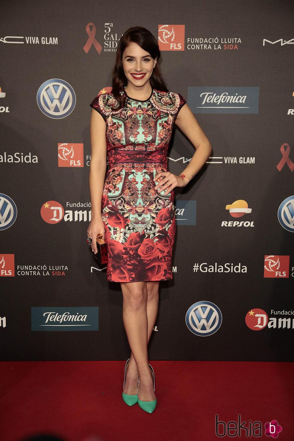 65878dcb6 Anterior Andrea Duro con vestido corto de estampado abstracto y rosas rojas