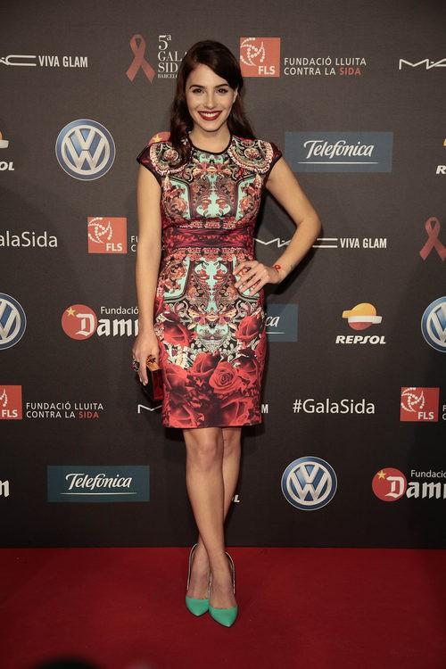 Andrea Duro con vestido corto de estampado abstracto y rosas rojas