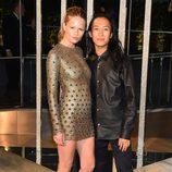 Anna Ewer junto a Alexander Wang con mini vestido ajustado en dorado y botas militares negras