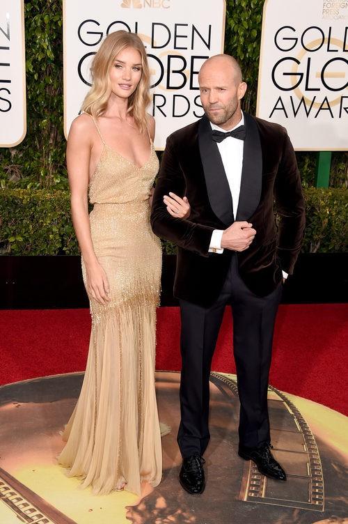 Rosie Huntington-Whiteley con vestido nude y detalles dorados de Saint-Laurent junto a Jason Statham