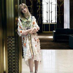 Natalia Vodianova con abrigo 3/4 blanco con detalles bordados de Prada