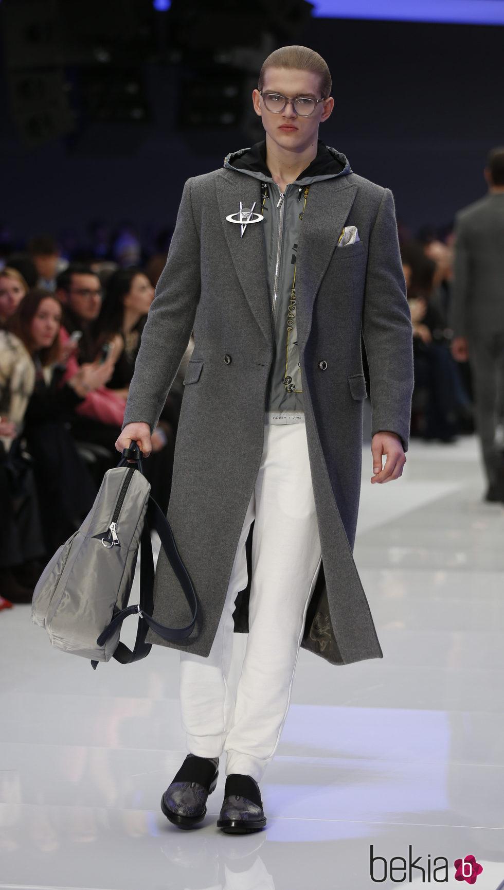 Abrigo tres cuartos gris con broche metalizado y pantalones blancos ...