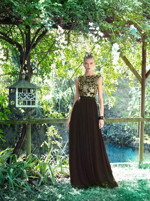 Vestido negro con motivos vegetales dorados en el cuerpo y falda plisada de vuelo de Carla Ruiz