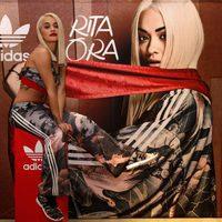 Rita Ora con ropa deportiva posando con el cartel de la nueva campaña para Adidas