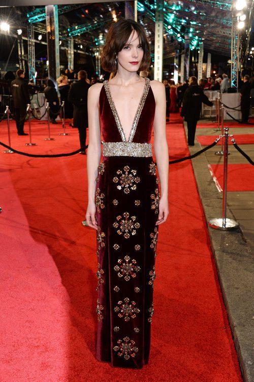 Stacy Martin con un modelo de terciopelo rojo con detalles brillantes en la alfombra roja de los BAFTA 2016
