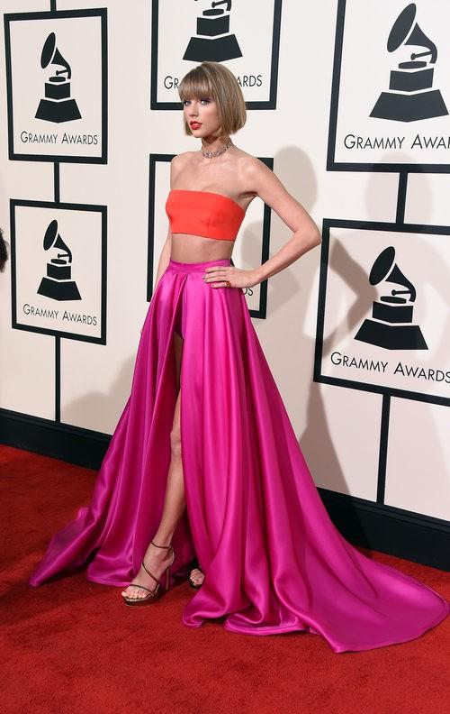 Taylor Swift con un vestido de dos piezas en color rojo y rosa en la alfombra roja de los Premios Grammy 2016