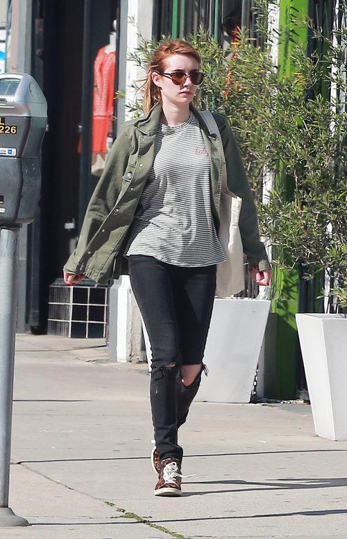 Emma Roberts con abrigo verde militar, pantalón roto y camisa a rayas