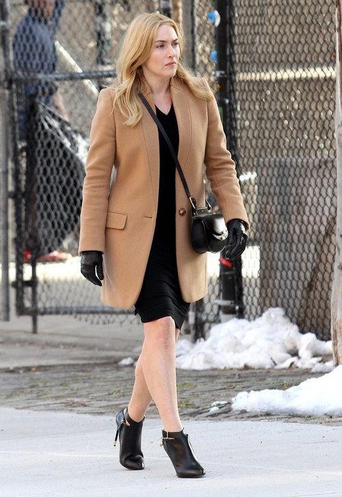 Kate Winslet con abrigo marrón y vestido negro más complementos