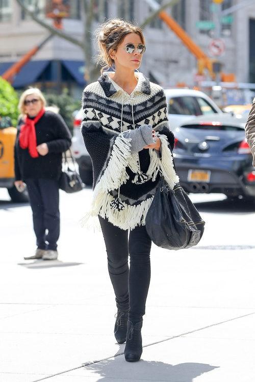 Kate Beckinsale con poncho tejido, pantalón y botines negros