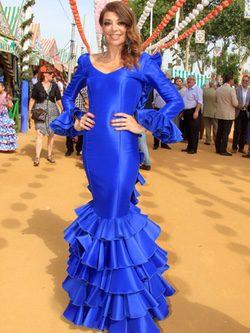 Lucia Hoyos con traje liso azul en la Feria de Abril de Sevilla.