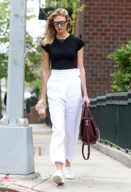 Karlie Kloss con pantalón blanco básica negra y tenis