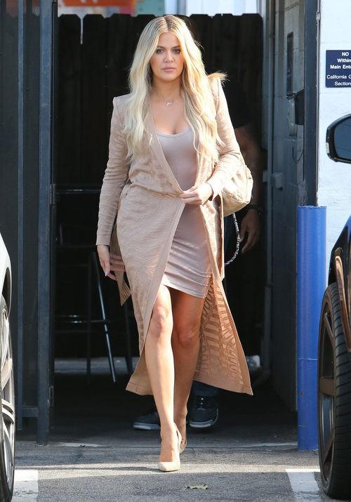 Khloe Kardashian con vestido corto y abrigo largo color carne