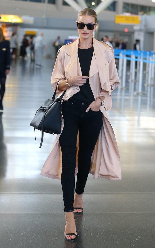 Rosie Huntington con aoutfit negro y abrigo color  rosa cuarzo