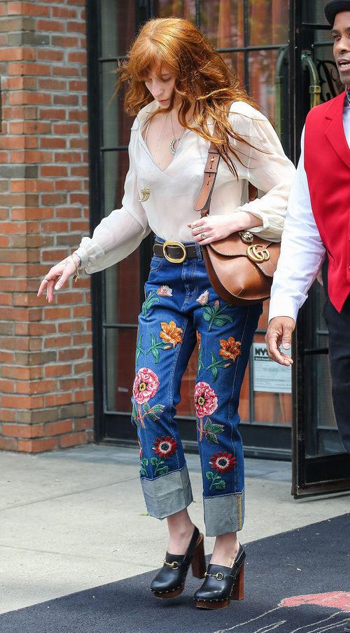Florence Welch con unos jeans con flores bordadas y una blusa beige transparente