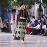 Modelo con camisa con transparencias y falda larga print de Chanel en el desfile Crucero 2017