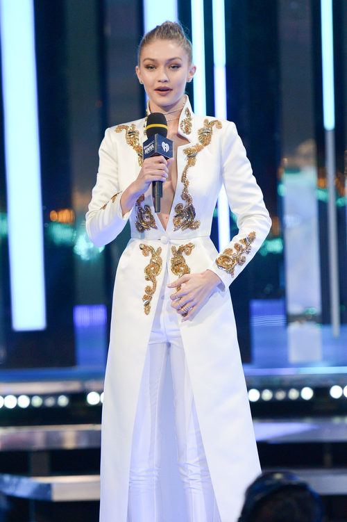 Gigi Hadid con un conjunto de traje chaqueta en blanco con toques dorados