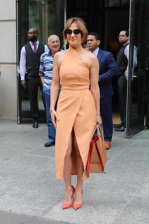 Jennifer Lopez con un vestido con apertura ladeada en naranja