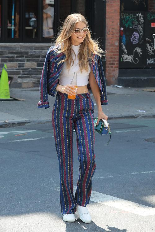 Gigi Hadid con un conjunto de pantalón y chaqueta a rayas estilo ochentero