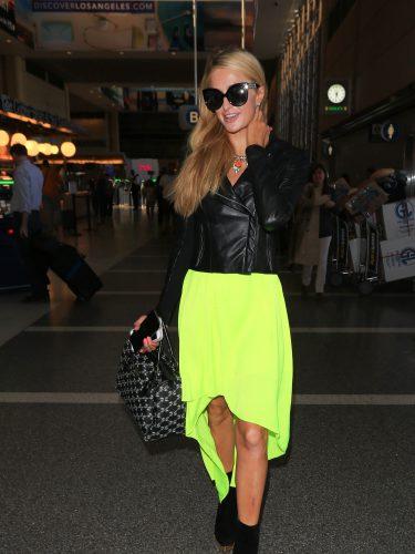 Paris Hilton con un total look de cazadora de cuero y vestido fluor