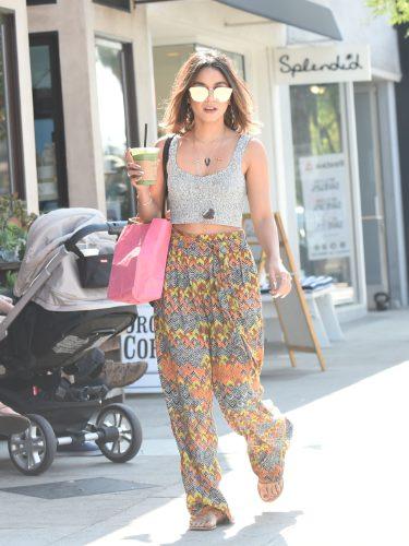 Vanessa Hudgens con un look de crop top metalizado y un pantalón palazzo