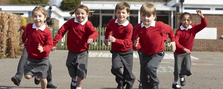 Niños de uniforme jugando en el cole