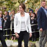 Kate Middleton con pantalón negro y americana blanca en su viaje a Canadá